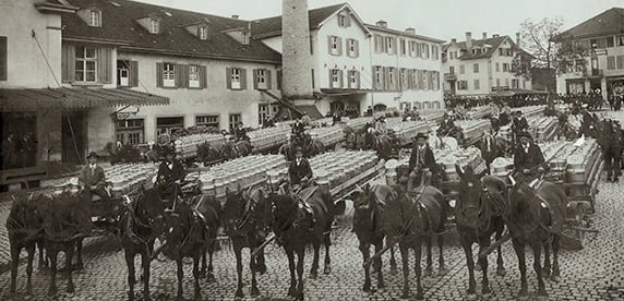 Foto de varios carruajes transportando los productos Neslté